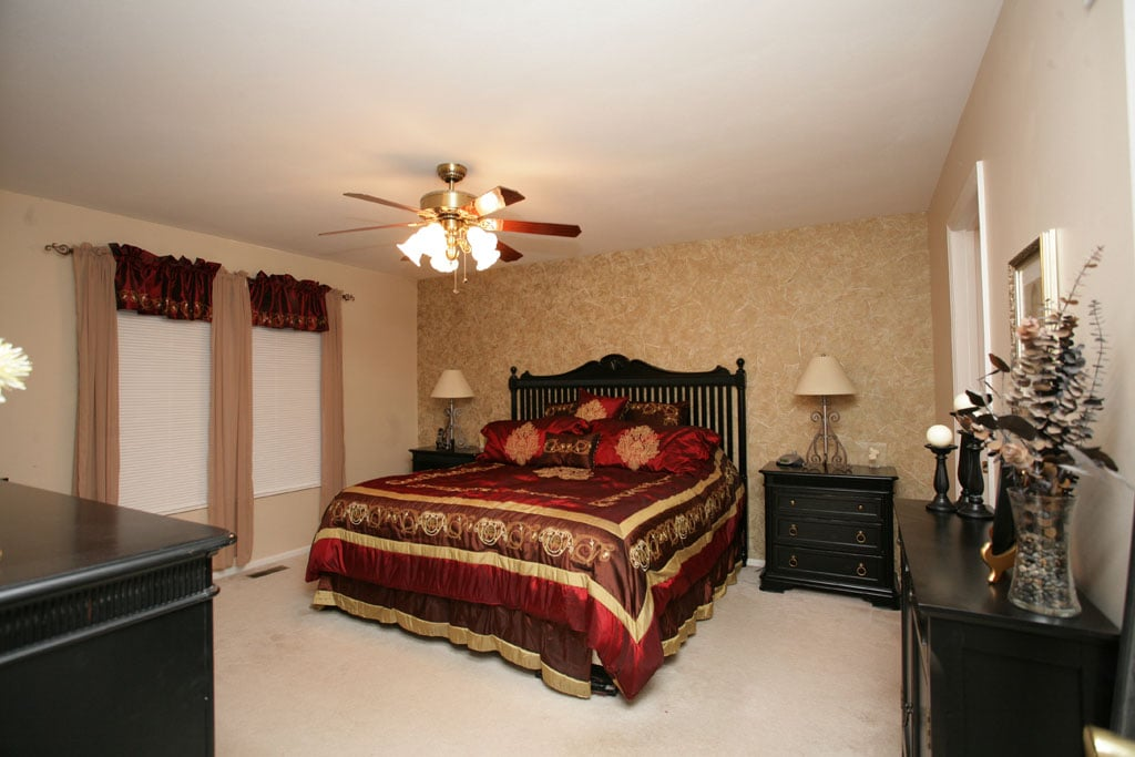The master suite with wallpaper on the wall at the head of the bed and a ceiling fan.