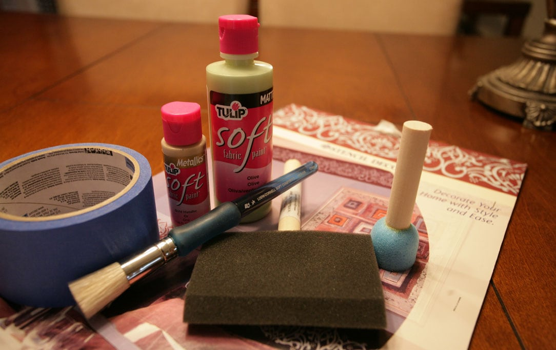 A paint brush, tape, and paint laid out for the project.