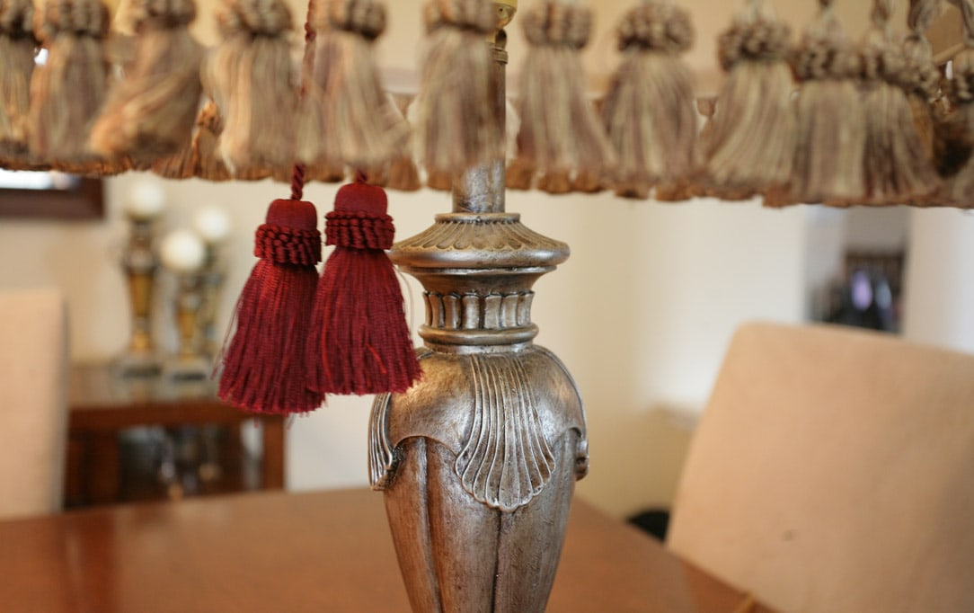 The base of the lamp with red and gold tassels hanging down.