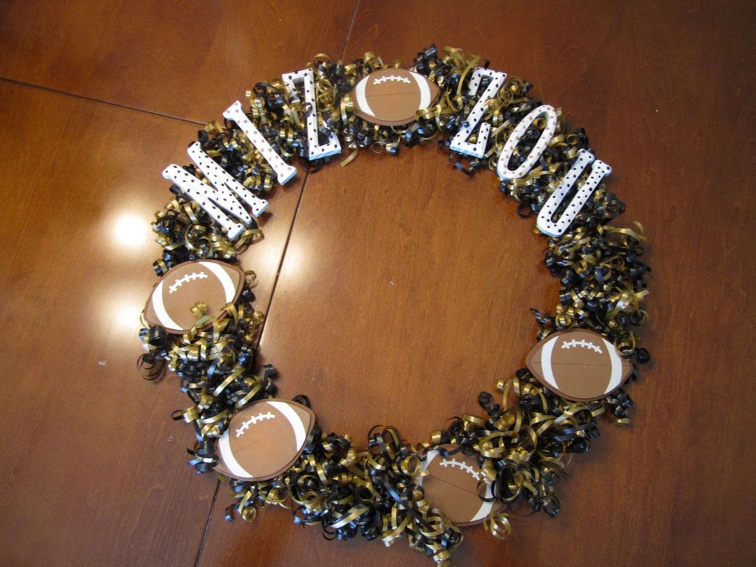Using the hot glue gun to put the letters and footballs on the wreath.