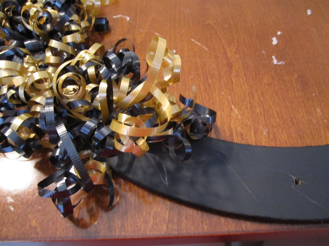 The curled black and gold ribbon on the wreath.