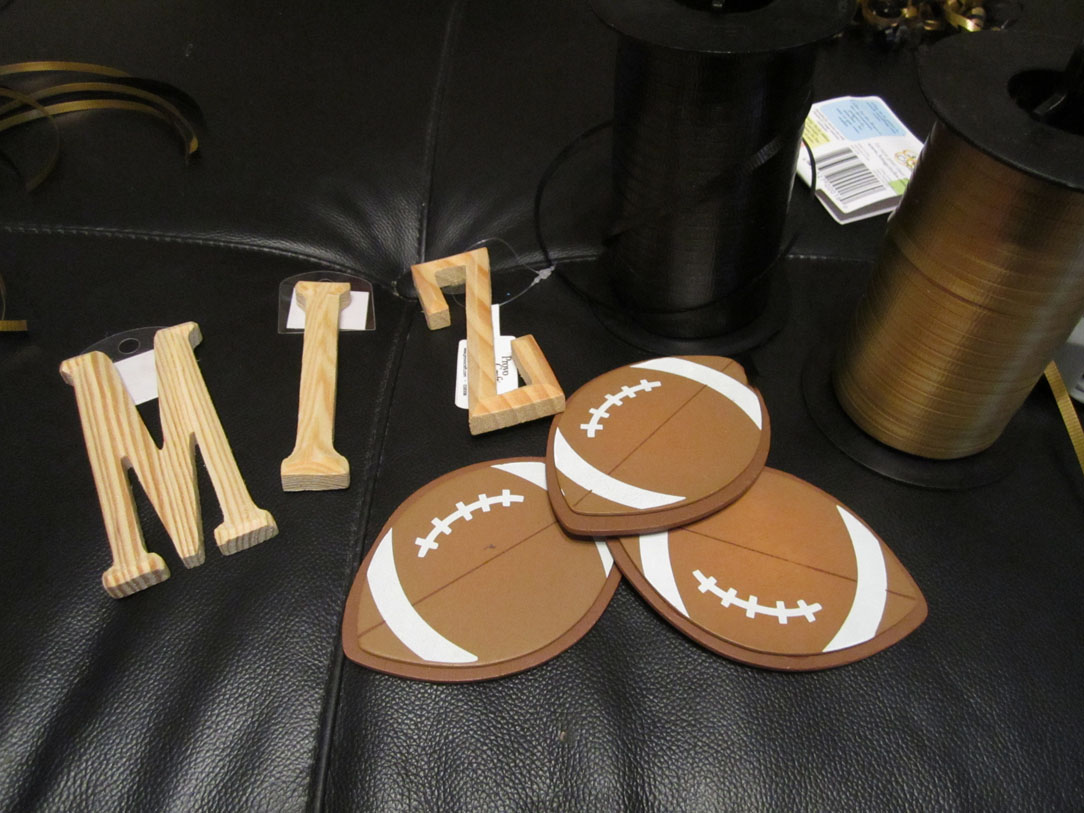 A cutout of footballs and the letters for the wreath.