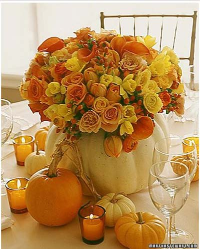 pumpkin filled with yellow, orange, and gold flowers on table.