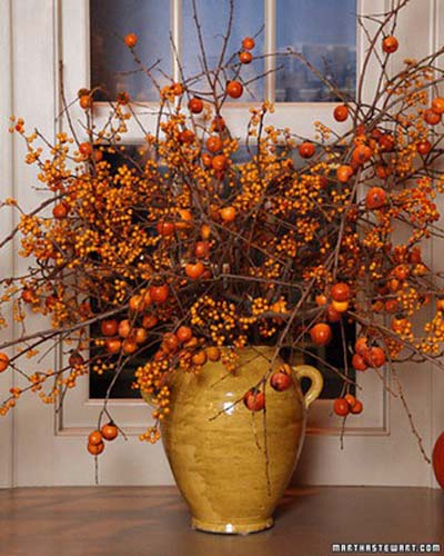 Gold vase filled with branches of orange and gold berries.