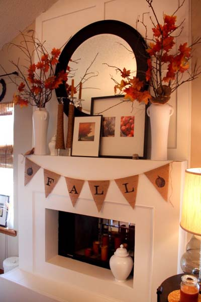 Burlap fall mantel flag on white mantel and large vases of red leaves and a large mirror on the wall.