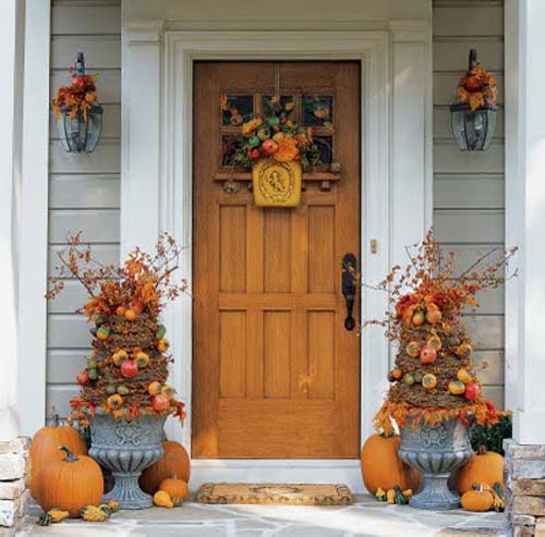 Front door of house with topiaries in ornate outdoor planters and pumpkins around them.