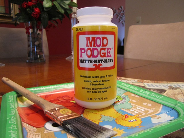 A bottle of mod podge and a brush beside it.