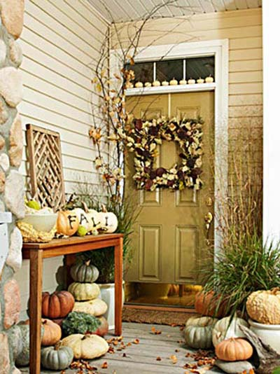 Wreath on pale yellow front door and pumpkins on the porch and outdoor side table.