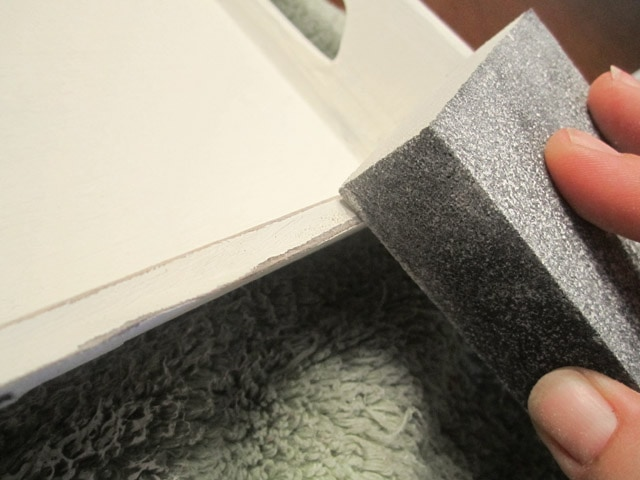 Using a sponge to paint the tray white.
