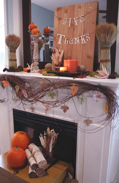 Fireplace mantel decorated with branches and pumpkins.