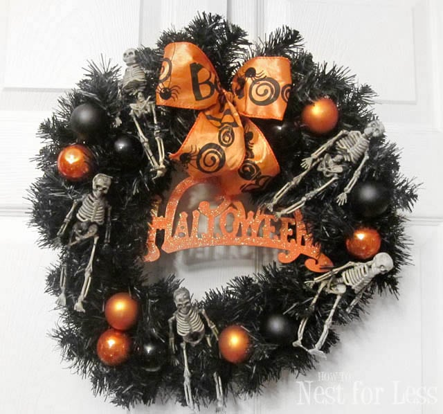 Halloween wreath with orange bow and skeletons.