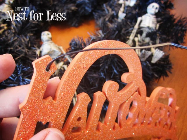 Tying the glitter Halloween sign to the wreath.