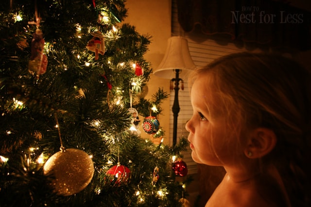 Little girl looking at the decorated Christmas tree.