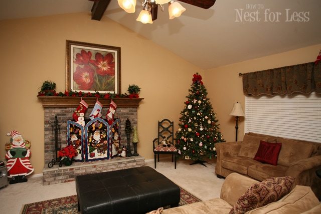 A Christmas tree in the corner, fireplace mantel, and Santa beside the mantel.