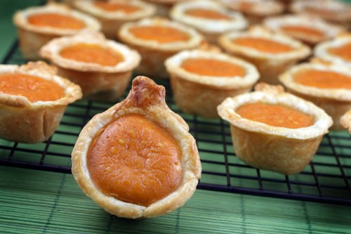Mini pumpkin pies on a cooling rack.