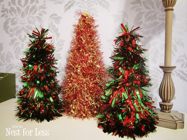 Three mini cone tinsel trees on a table.