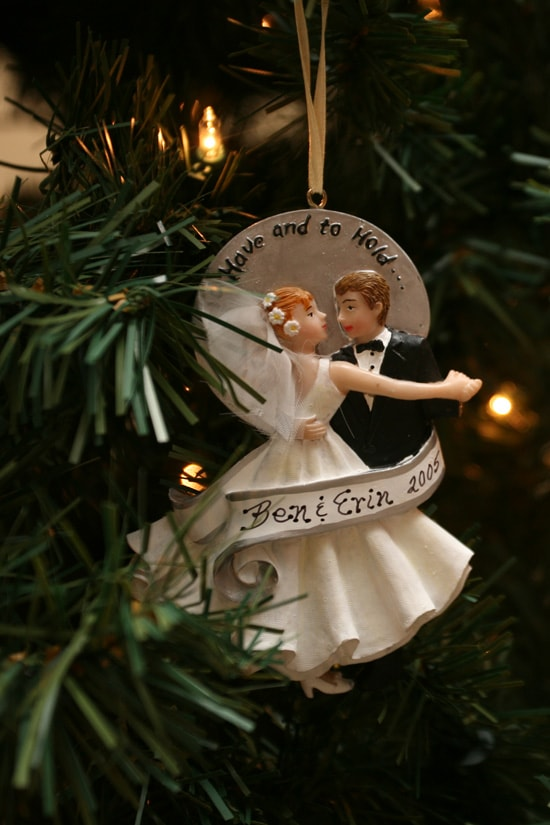 A bride and groom ornament hanging on the tree.