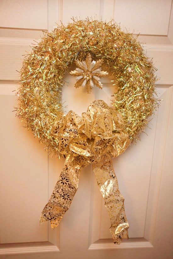 A gold tinsel wreath on the front door.