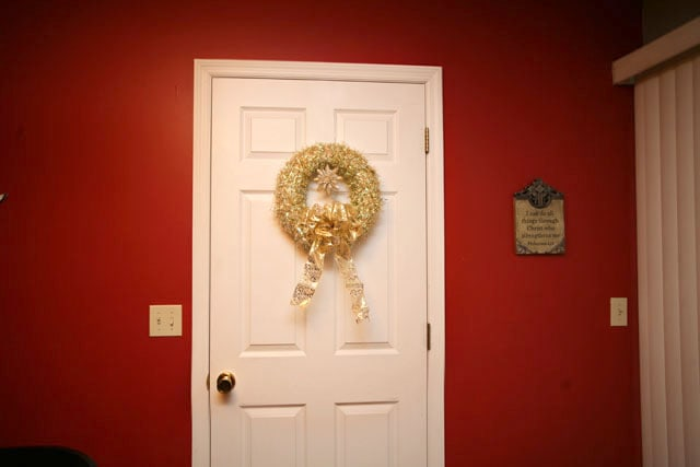 A red wall, white door and a gold wreath.