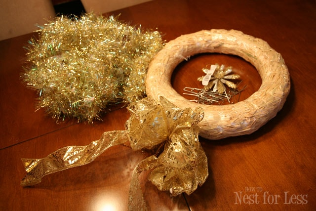 A wreath circle, gold tinsel and a gold bow on the floor.