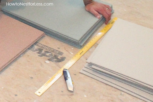 The tiles in a stack on the floor with facto knife and ruler.
