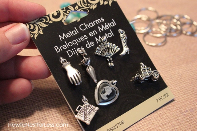 Metal charms in the package being held up.