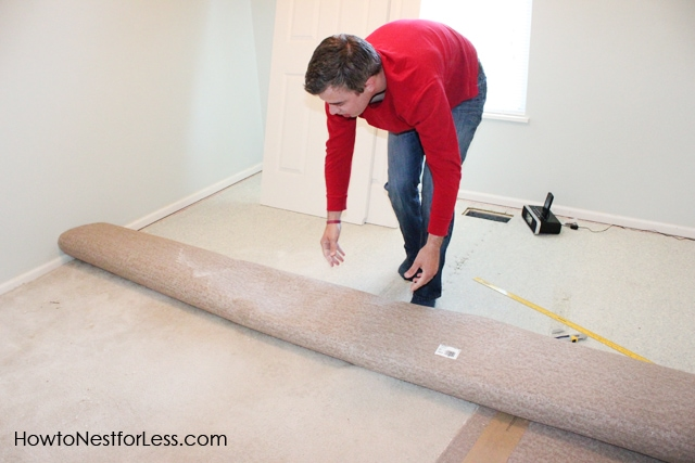 Man in red shirt rolling up the dirty carpet.