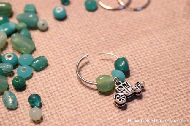 The metal charm and the blue, green stones on the wire.