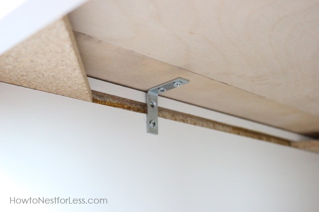 Attaching the metal bracket to the underside of the plywood.