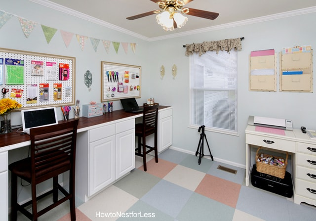 Craft room with long desk and two chairs.
