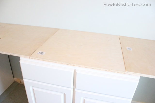 Putting the plywood top on the white base cabinets.