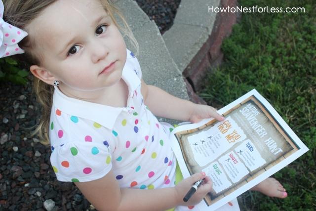 Little girl holding a scavenger hunt paper.