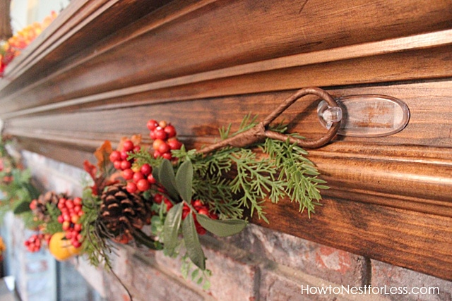 Clear hooks holding up the garland on the fireplace.