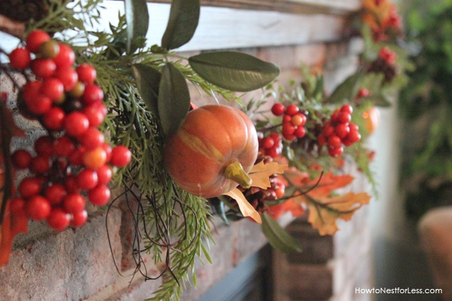 Fall garland with berries and pumpkins on the front of the fireplace.