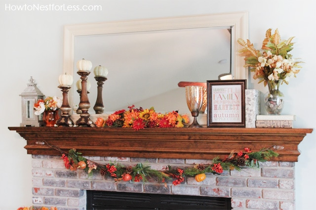 Fireplace mantel with autumn leaves and candle stick holders with pumpkins on them.