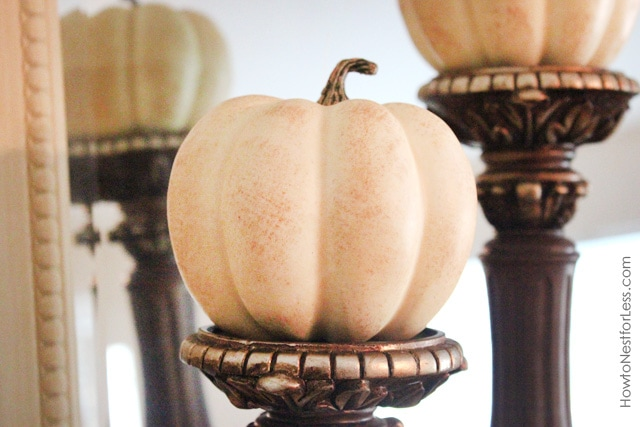 Candlestick holders with white mini pumpkins on top.