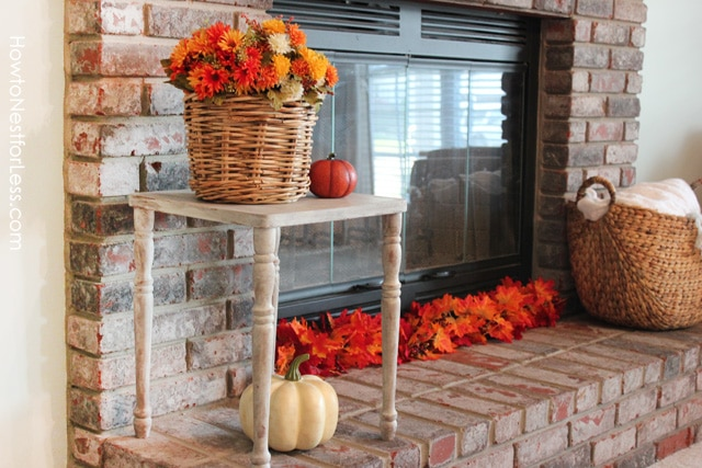 A basket of flowers on a table by the fireplace and red and orange leaves in front of the fireplace.