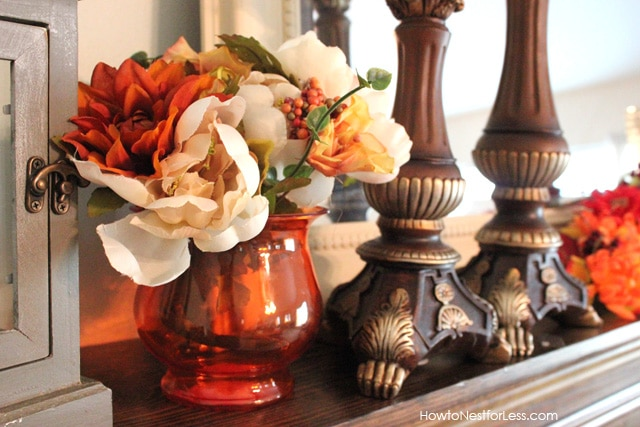 Red vase filled with white and orange flowers on the mantel.