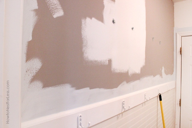 The wall in the laundry room half painted.
