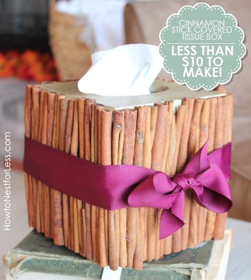 Cinnamon stick tissue box with a purple ribbon around it.
