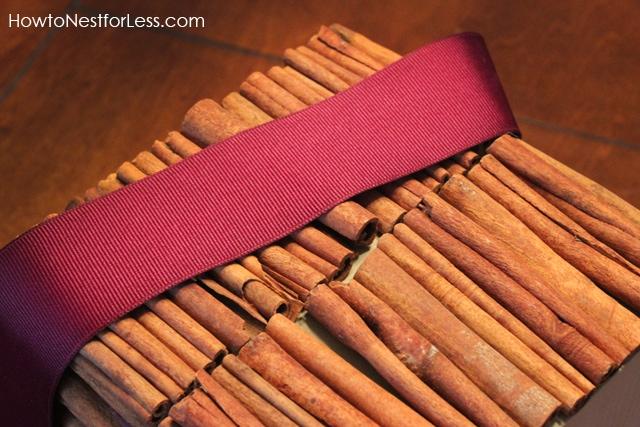 Tying a purple ribbon around the cinnamon tissue box.