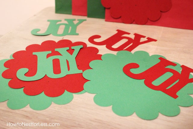 The word Joy cut out on the table in green and red.