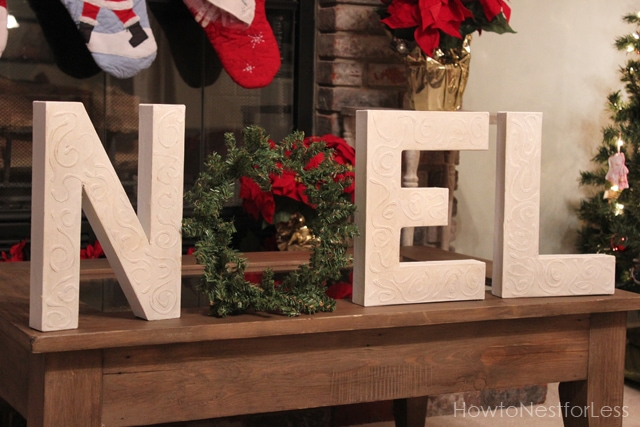 Noel spelled out on the table in front of the fireplace.