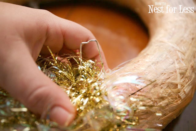 Using pins to put the tinsel on the wreath.