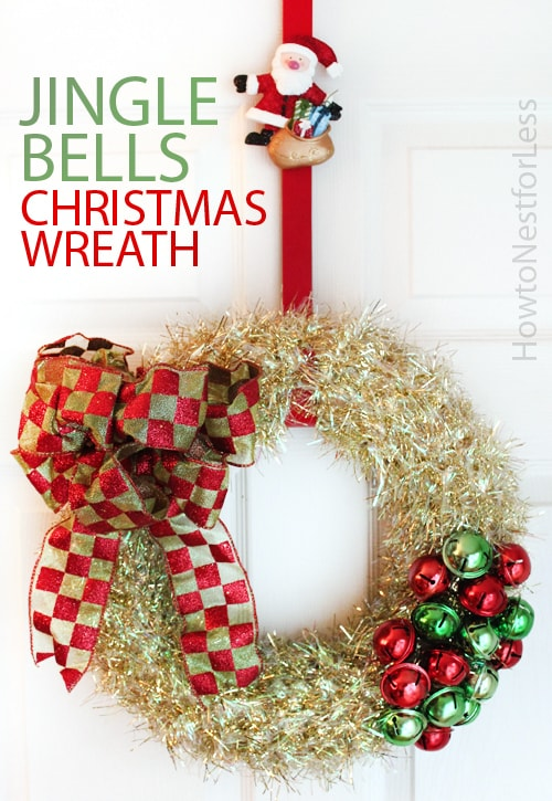 A holiday wreath with a large bow, jingle bells and a Santa on the ribbon.