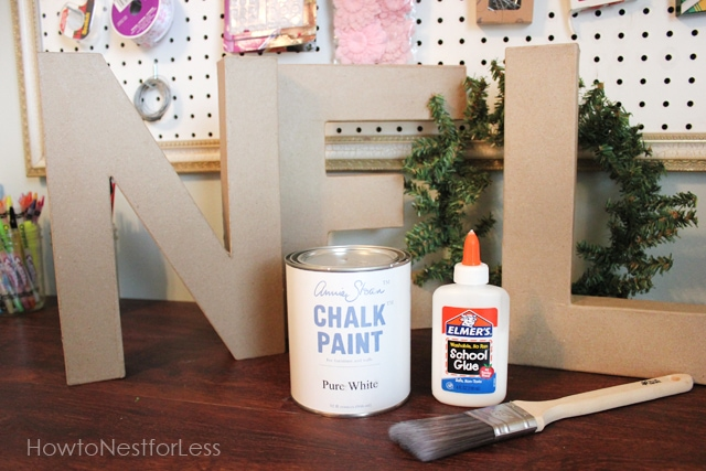 Chalk paint, glue, and brush in front of the N on the sign.