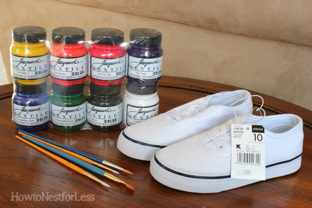 New tennis shoes, paint brushes and paint on the table.