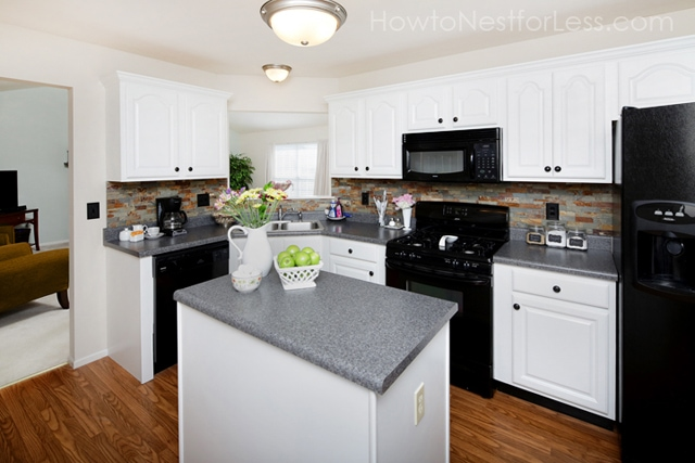 White painted cabinets with black appliances and grey counter tops