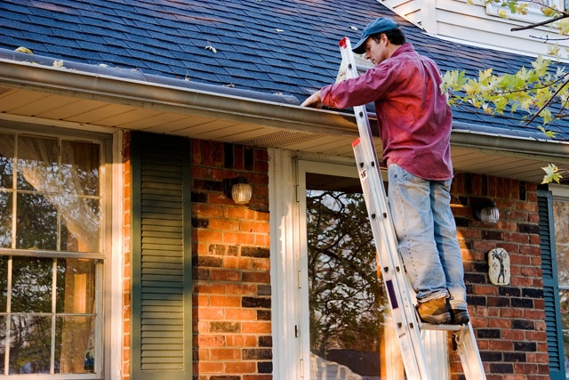 bigstock-Man-Cleaning-Gutters-9331940