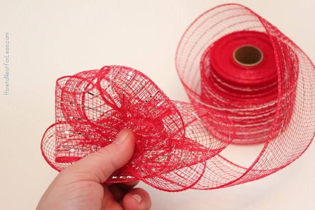 Holding the red mesh ribbon between two fingers.